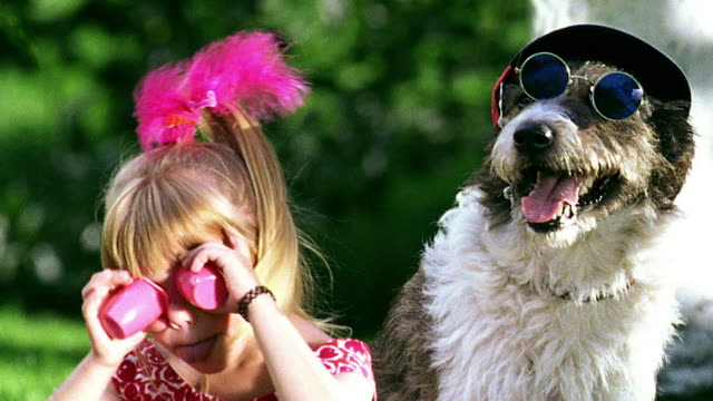 stockvideo's en b-roll-footage met close up girl playing with cups over eyes + sticking tongue / dog with sunglasses + hat next to girl - hoed