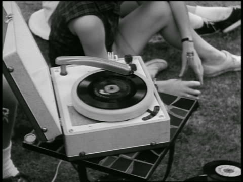 b/w 1955 close up girl sitting on ground with coke bottle next to phonograph playing 45 rpm record outdoors / industrial - record player stock videos & royalty-free footage