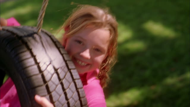 vídeos de stock e filmes b-roll de close up girl smiling at cam while riding in tire swing outdoors - 4 5 anos