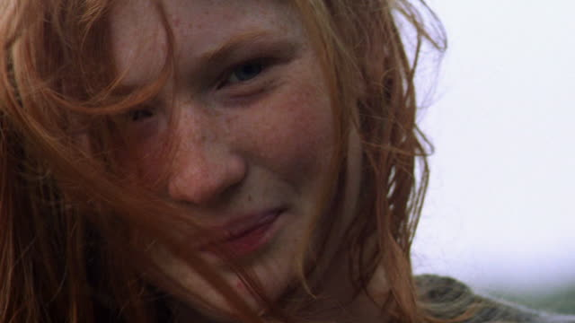 close up girl smiling + tilting head with red hair blowing in wind over face / kilkenny county, ireland - one woman only点の映像素材/bロール