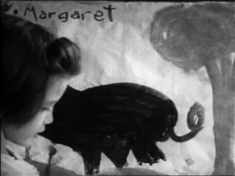 vidéos et rushes de b/w 1945 close up girl standing in front of painting of pig / educational - seulement des petites filles