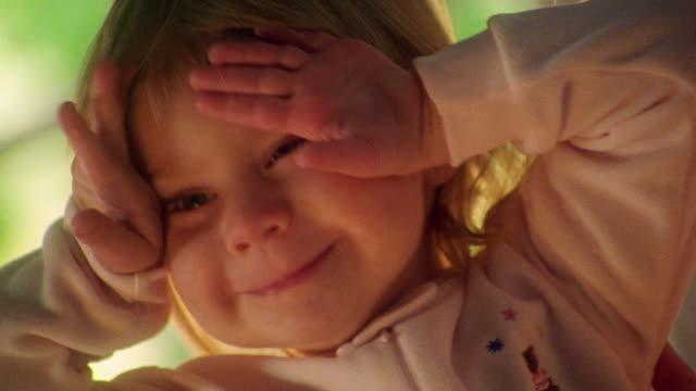 close up girl toddler covering eyes with hands + uncovering eyes indoors - augen zuhalten stock-videos und b-roll-filmmaterial