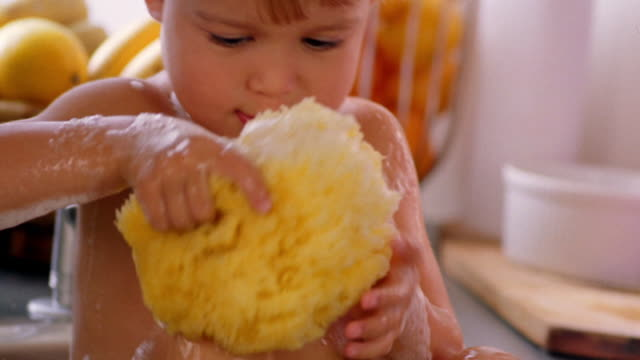 stockvideo's en b-roll-footage met close up girl toddler washing + playing with sponge in sink - alleen één meisje