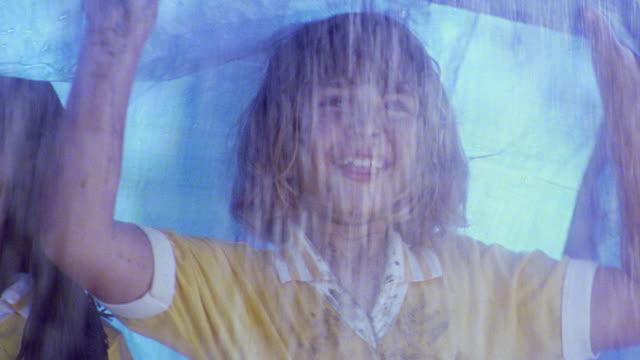 close up pan girls in muddy uniforms under tarp in rain / girl looking up + sticking out tongue to rain - blöt bildbanksvideor och videomaterial från bakom kulisserna