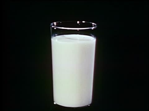 1948 close up glass of milk / industrial - いっぱいになる点の映像素材/bロール