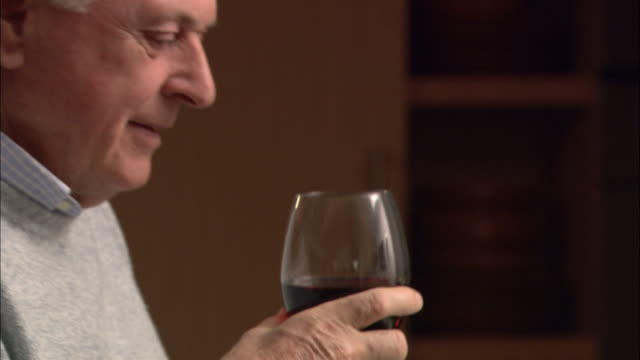 Close up glass of red wine / pan man picking up glass and drinking wine / zoom out woman bringing plate of bread to table and sitting down / man pouring olive oil on bread
