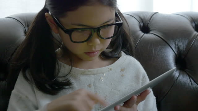 Close up glasses girl using tablet on sofa