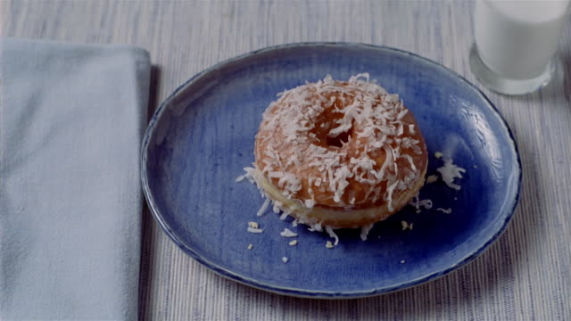 Close up glazed doughnut being picked up off plate