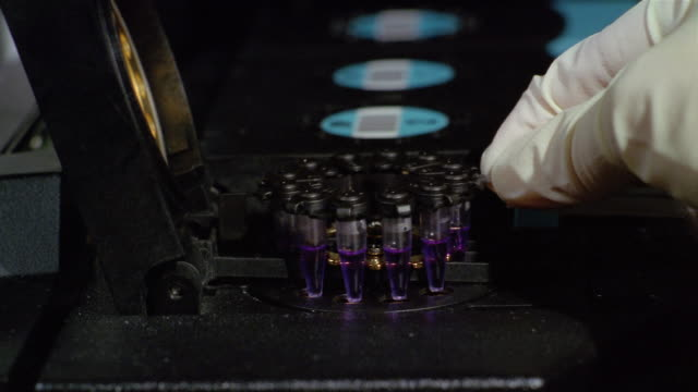 Close up gloved hand placing nucleic acid sample into DNA purification system / removing sample