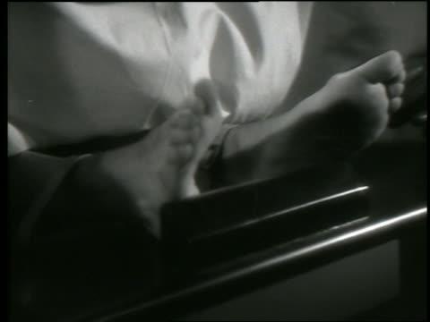 B/W close up gloved hands put restraints on dead man's feet