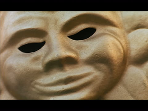 close up gold handheld masquerade mask - breitwandformat stock-videos und b-roll-filmmaterial