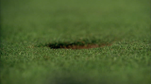 Close up golf ball rolling into hole