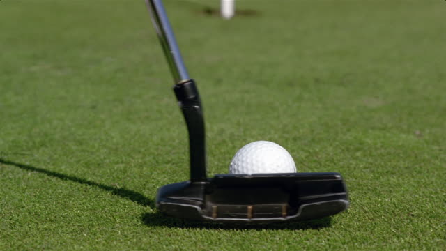close up golf club putting golf ball / missing hole - bandierina da golf video stock e b–roll