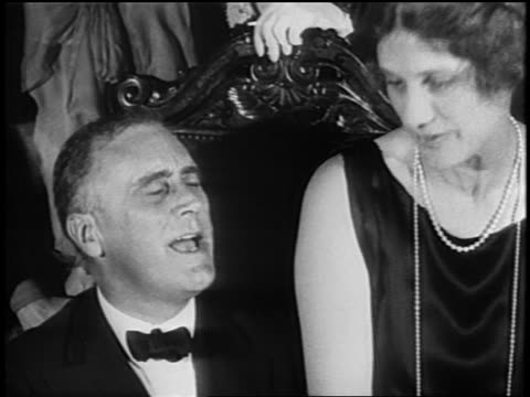 vídeos y material grabado en eventos de stock de close up governor f.d. roosevelt in tuxedo sharing chair with mrs. lehman + talking / newsreel - 1928