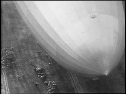 b/w 1929 aerial close up graf zeppelin flying very low over ground / people walk alongside / lakehurst, nj - airship stock videos & royalty-free footage
