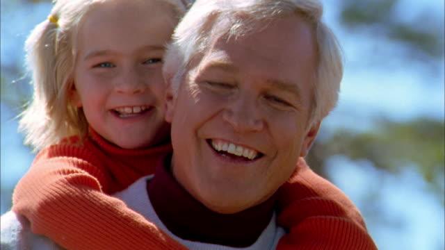 close up grandfather and granddaughter smiling at cam - おんぶ点の映像素材/bロール