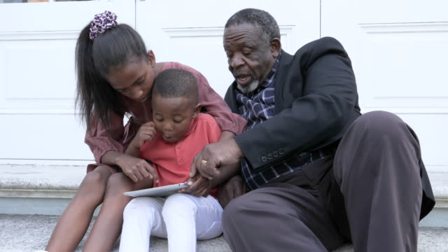 vidéos et rushes de close up, grandfather and grandkids uses digital tablet - s'appuyant