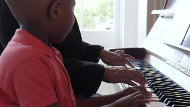 close up, grandmother and grandson play piano - legame affettivo video stock e b–roll