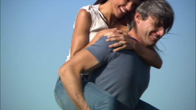 close up grass/ tilt up man giving woman piggyback ride/ man covering woman's eyes with her hands/ man and woman spinning and laughing/ umbria - 25 29 jahre stock-videos und b-roll-filmmaterial