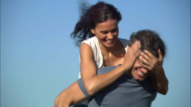 vídeos de stock, filmes e b-roll de close up grass/ tilt up man giving woman piggyback ride/ woman covering man's eyes with her hands/ man and woman spinning and laughing/ umbria - mãos cobrindo olhos