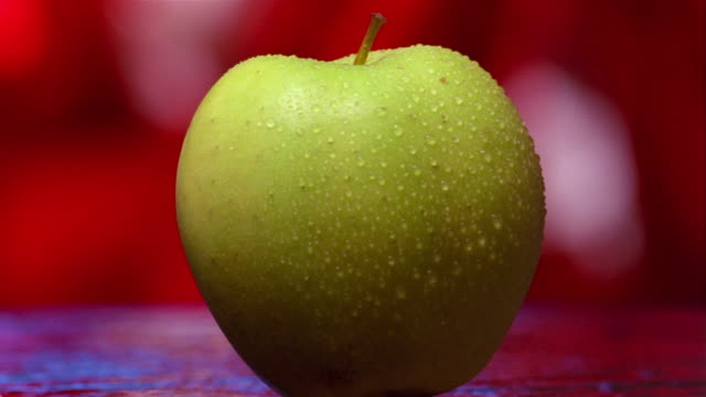 close up green apple being cut in half - auseinander stock-videos und b-roll-filmmaterial