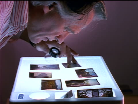 vídeos de stock e filmes b-roll de close up grey-haired man examining transparencies with magnifying glass - lupa