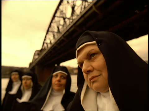 vídeos de stock, filmes e b-roll de close up group of nuns standing under bridge bobbing heads to beat of music / prague - imagem tonalizada