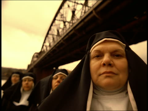 vídeos de stock, filmes e b-roll de close up group of nuns standing under bridge bobbing heads to beat of music / prague - nun