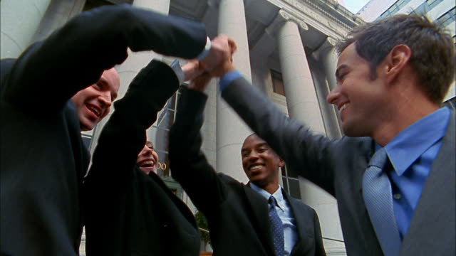 close up group of young business people clasping hands - avvocato video stock e b–roll