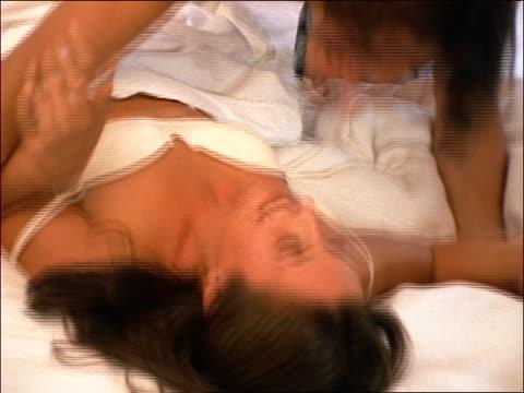 close up half-undressed couple rolling around on bed - heterosexuelles paar stock-videos und b-roll-filmmaterial