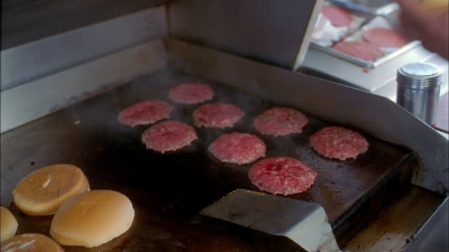 close up hamburgers being flipped on grill in fast food restaurant - ファーストフード点の映像素材/bロール