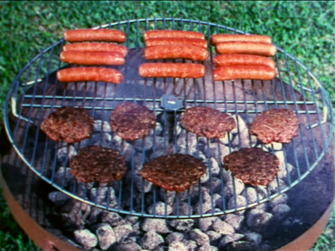 1960 close up hamburgers + hot dogs cooking on grill outdoors / travelogue - hamburger stock videos & royalty-free footage