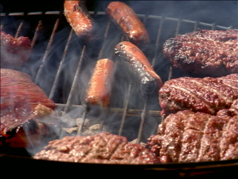 close up pan hamburgers, steaks + hot dogs on smoky grill - medium group of objects stock videos & royalty-free footage