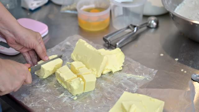 クッキーを調理するための手切りバターをクローズアップ - 調理用へら類点の映像素材/bロール