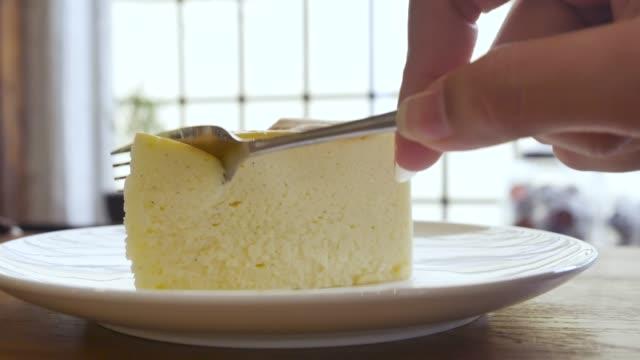 vídeos de stock, filmes e b-roll de fechar a mão corte cheesecake - garfo