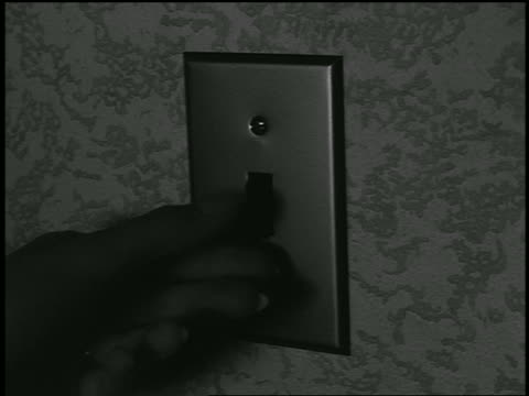 b/w 1955 close up hand flipping up light switch / industrial - light switch stock videos & royalty-free footage
