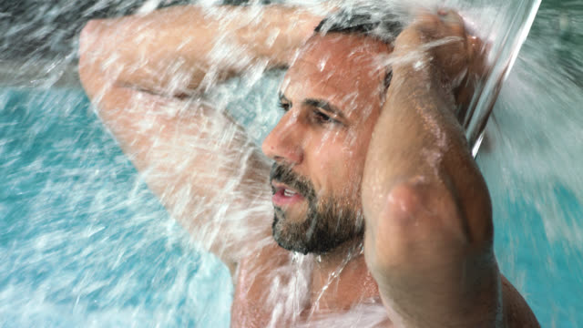 hotel day spa indoor swimming pool with thermal spring water torrent shower – attractive sporty buff muscular tanned sexy man in his 30s with short dark hair and trimmed beard enjoys the massaging splashing foaming waters while washing hair - virility man - hand in hair stock videos & royalty-free footage