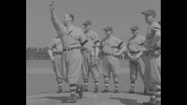 close up hand holding baseball with brooklyn dodgers printed on it / medium shot dodgers manager burleigh grimes throws ball as players look on /... - spring training stock videos & royalty-free footage