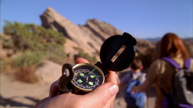 stockvideo's en b-roll-footage met close up hand holding compass / family walking away from cam on hiking trail - begeleiding