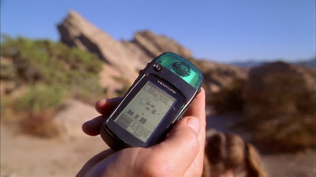close up hand holding electronic gps device / family walking away from cam on hiking trail - global positioning system stock videos & royalty-free footage