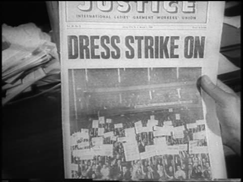 "close up hand holding newspaper with headline ""dress strike on"" / garment workers strike / newsreel - newspaper strike stock videos & royalty-free footage"