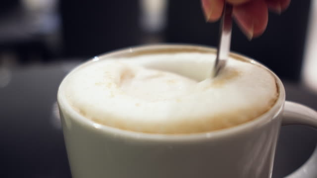 close up hand holding spoon stirring milk foam of cappucino coffee on white cup