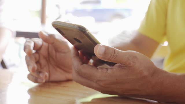 vídeos y material grabado en eventos de stock de de cerca de hombres de negocios asiáticos de 20 a 30 años de edad usando ropa casual, usando un teléfono o un teléfono inteligente para chatear - en búsqueda