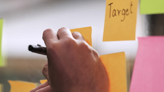 close up hand of asian businessman wear suit writing on sticky note for brainstorming ideas on clear whiteboard at modern office. analyze and synthesis project - adhesive note stock videos & royalty-free footage