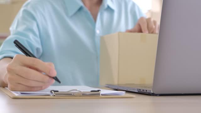 närhand av asiatisk småföretagare som skriver order från kund till leverans hemma med lagerkontroll på laptop.online småföretags e-handelskoncept - e post bildbanksvideor och videomaterial från bakom kulisserna