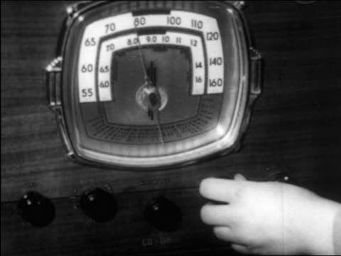 B/W 1940 close up hand of boy tuning dial of radio / documentary