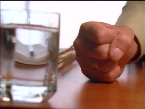 vidéos et rushes de close up hand of businessman pounding desk with fist / glass of water in foreground - fist