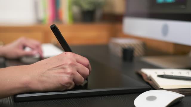stockvideo's en b-roll-footage met close-up hand van de ontwerper werkt op pen tablet op de desktop computer op kantoor - redacteur