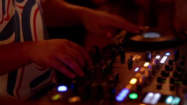 クローズアップ手のディージェイデッキ/ターンテーブルでディスコパーティーのナイトクラブ  - スクラッチ点の映像素材/bロール