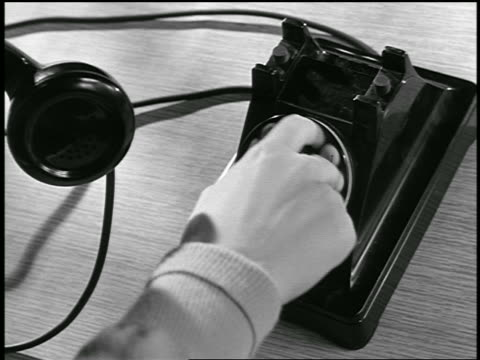 vidéos et rushes de b/w 1954 close up hand of man dialing rotary telephone / industrial - 1954